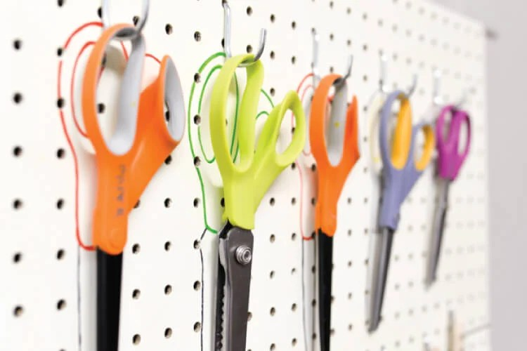 scissors organized on peg board with outlines