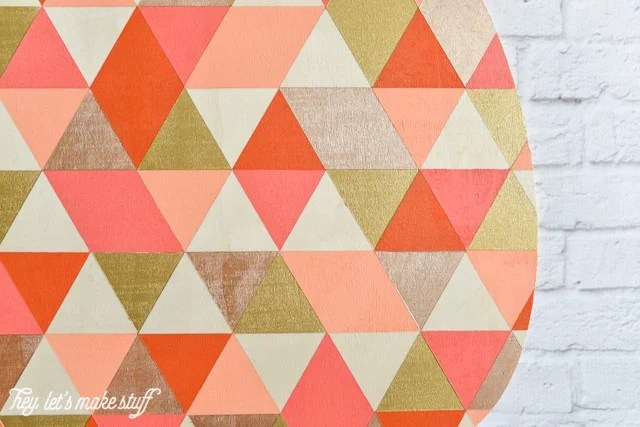 close up view of finished geometric painted pumpkin hanging on white brick fireplace