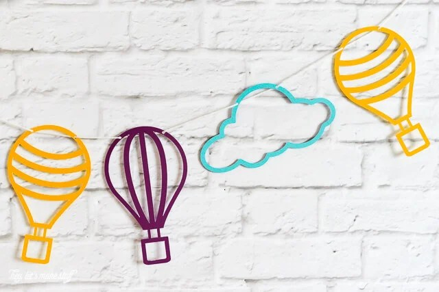 close up of colorful hot air balloon and cloud SVG files cut on paper and strung against background