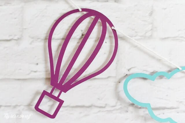 colorful hot air balloon and cloud SVG files cut on paper and strung against background
