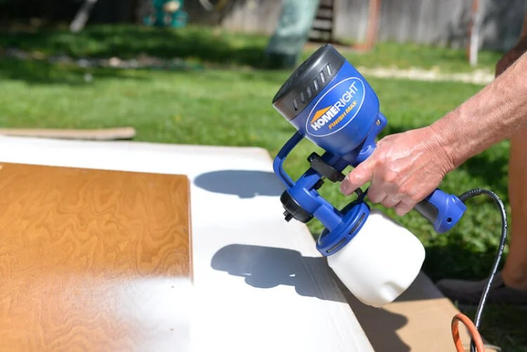 using a sprayer to paint kitchen cabinets