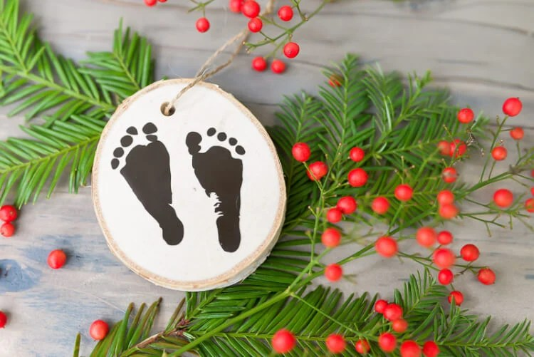 Use your Cricut Explore or other cutting machine to easily cut your newborn's footprints out of vinyl to make a sweet keepsake ornament.