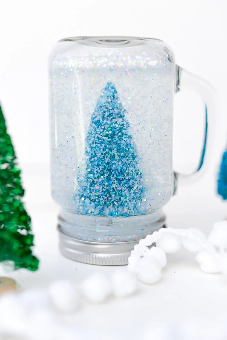 Make a glittery Mason Jar Snow Globe for Christmas this year! A great winter craft to make if you aren't expecting a White Christmas where you are. Can be used as a calm jar, too!