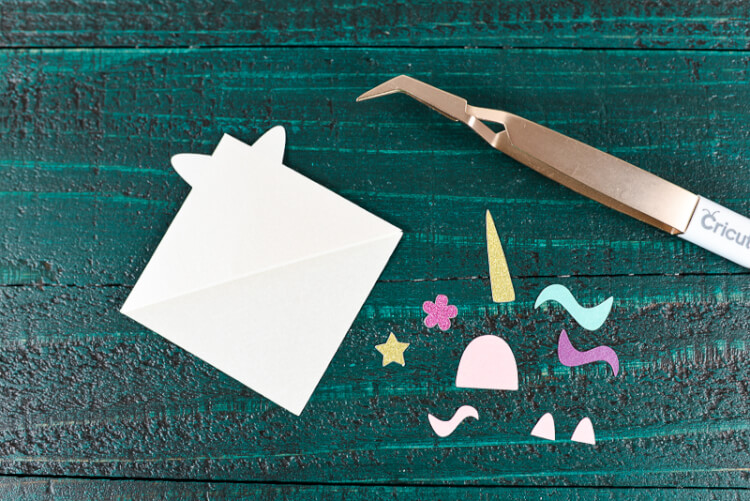 Fold the unicorn bookmark into a square - Make these adorable little unicorn bookmarks! The perfect craft for any time you're diving into a particularly whimsical book. A FREE SVG and DXF download.