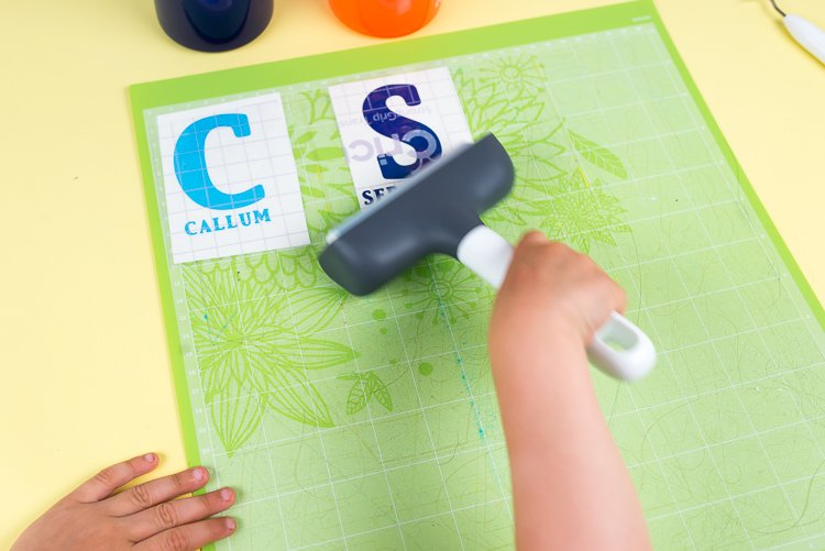 Use a scraper or brayer to press down transfer tape over text