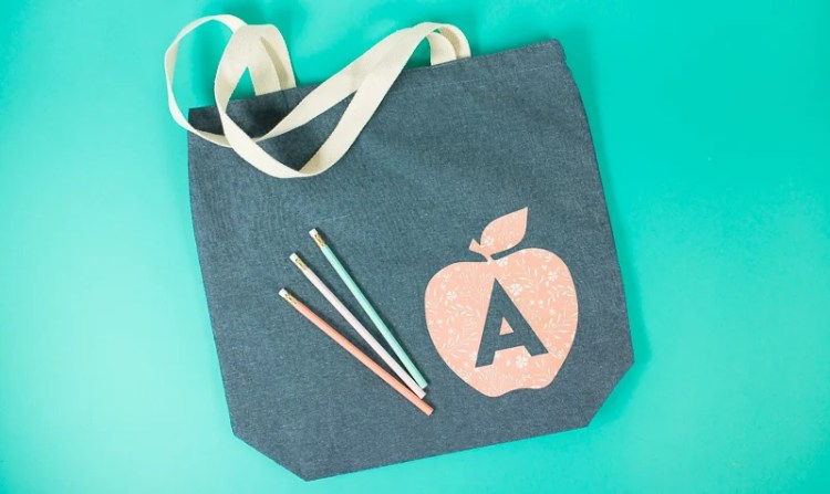 Looking for a quick project to make for your child's favorite teacher? She'll love this personalized apple tote bag! It's the perfect last minute teacher gift idea made with your Cricut or other cutting machine.