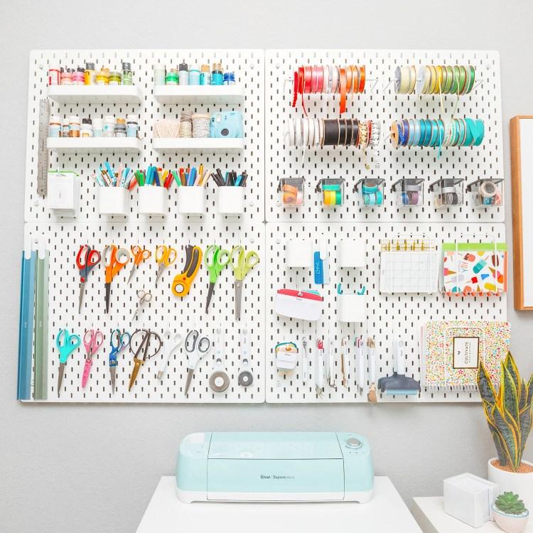 IKEA SKADIS pegboard holding craft supplies—great craft room organization!