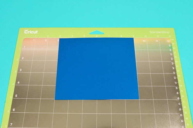 Then place your base material, like cardstock, on the mat, using the grid on the metal mat to align it.