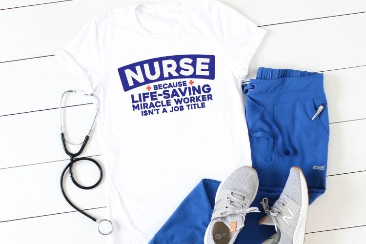 Nurse: Because Life-Saving Miracle Worker Isn't a Job Title image on a white shirt with blue scrubs and stethoscope.