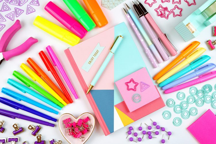 Art supplies on a table, including pens, paper, tacks, paper clips, craft supplies.