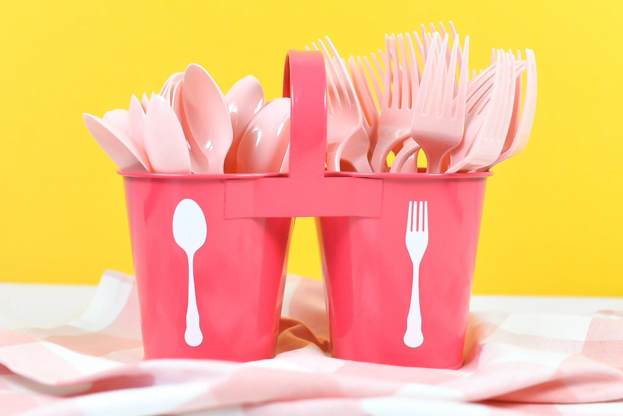 Pink utensil caddy with white spoon and for decals, filled with pink plastic forks and spoons on a yellow background.