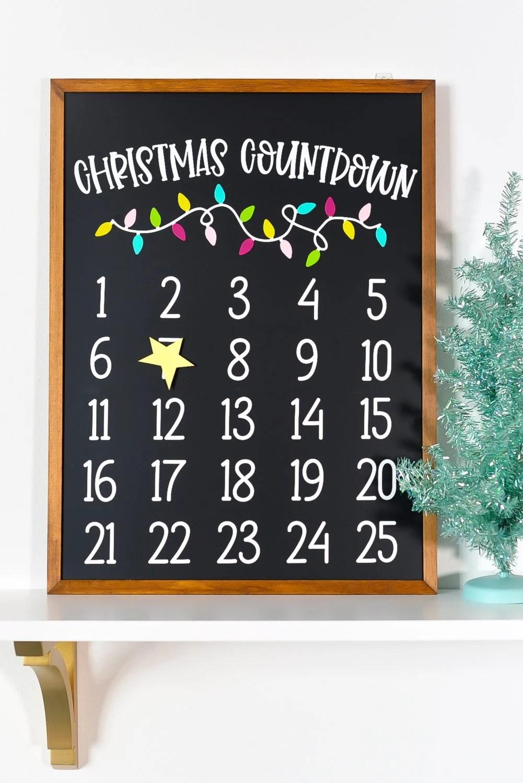 Christmas countdown calendar on a shelf with a faux Christmas tree.