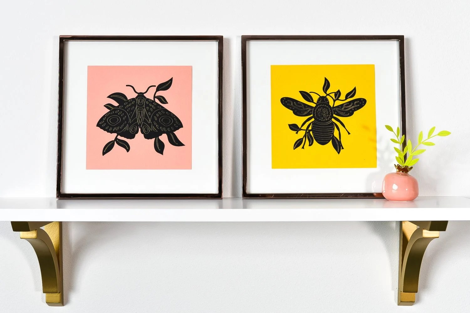 Moth and bee foiled artwork on a shelf with small bud vase and foiled plant.