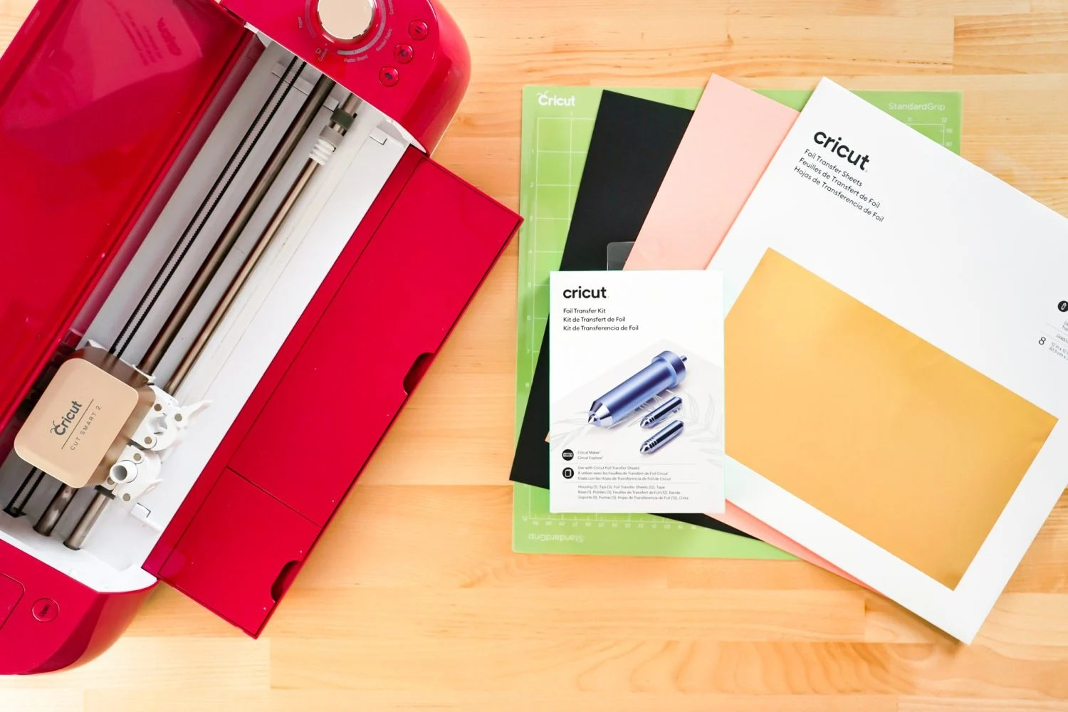 Overhead shot of supplies needed for this project: Cricut, mat, cardstock, foil, and foiling tool