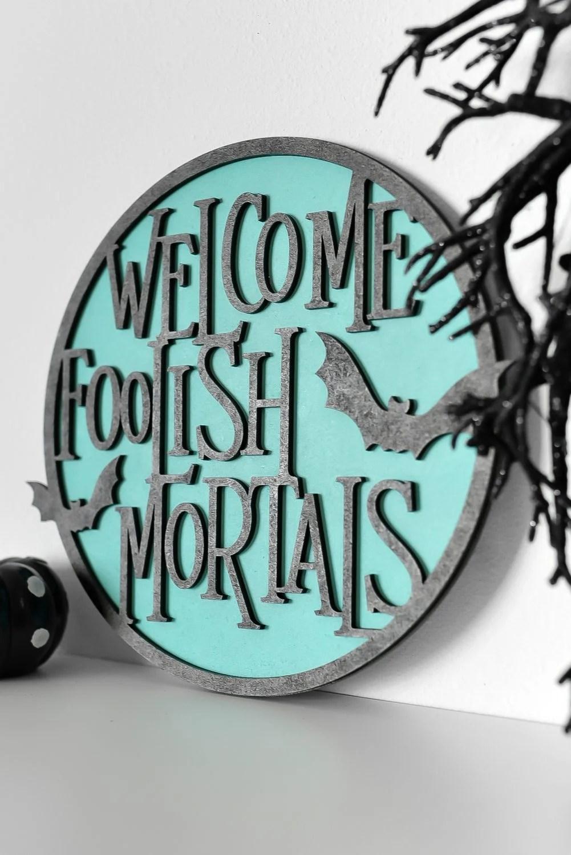Angled shot of Welcome Foolish Mortals sign on a shelf with Halloween decor