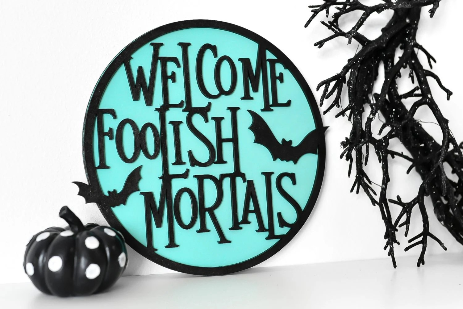 """Get ready for a ghoulish visit to the Haunted Mansion by crafting this """"Welcome Foolish Mortals"""" wood sign! This Halloween sign is made using the Glowforge, and can also be cut on a Cricut or other cutting machine."""