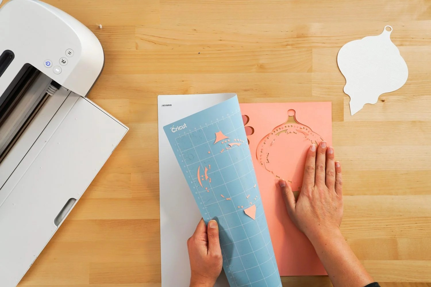 Hands removing pink cardstock from mat