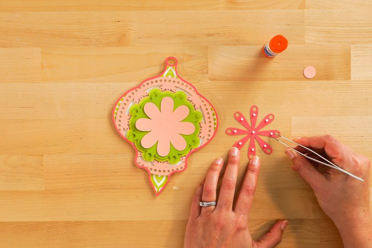 Hands gluing layers for the Christmas mandala
