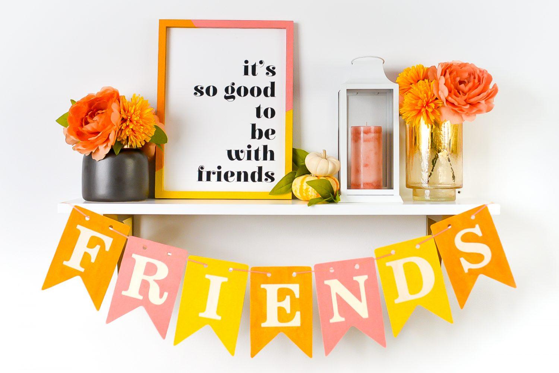 Friendsgiving decorations: friends sign, friends banner, faux flowers, candle in lantern, pumpkins