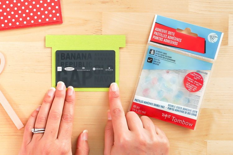 Hands gluing gift card to insert