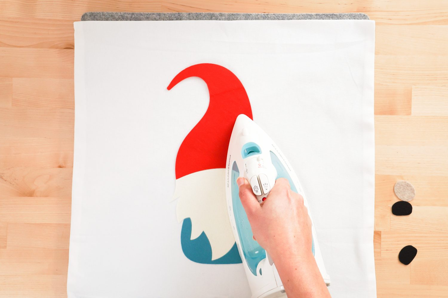Hand pressing the gnome with a household iron.