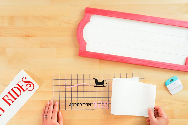 Hands peeling back backing sheet of pink layer.