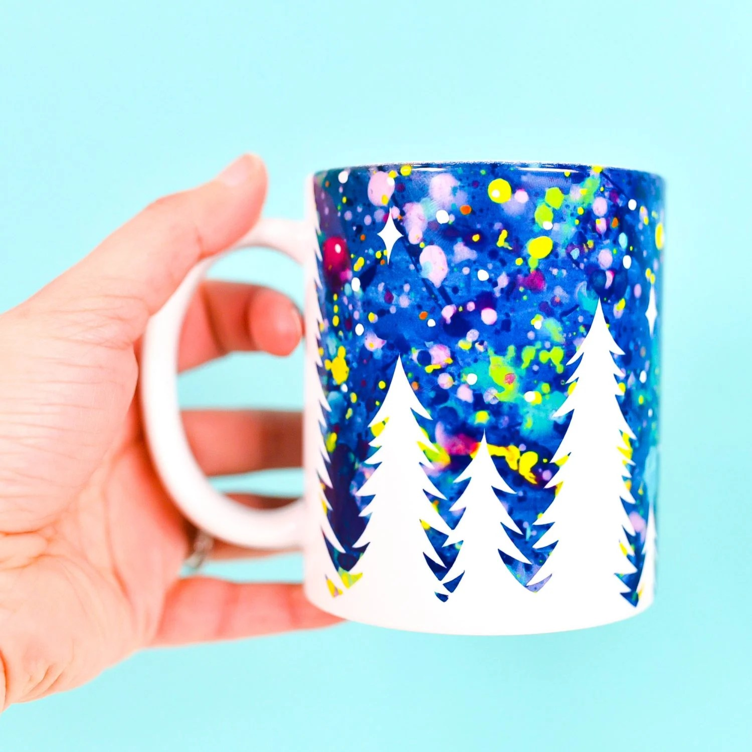 Hand holding finished mug with trees and starry sky