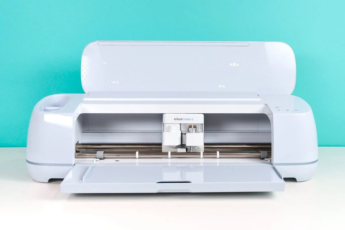 Open Cricut Maker 3 on table with teal background.