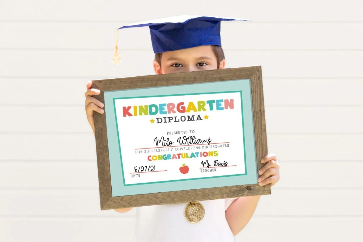 Child holding framed kindergarten diploma while wearing grad cap