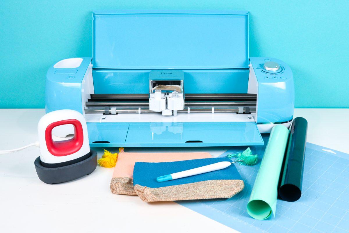 Blue Cricut Explore, EasyPress Mini, blue Cricut cutting mat, black and mint iron on vinyl, two makeup bags, and a weeding tool.