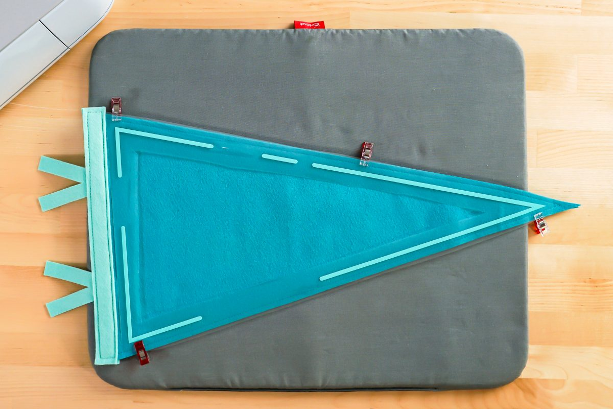 Sewn felt pennant with iron on border placed on top