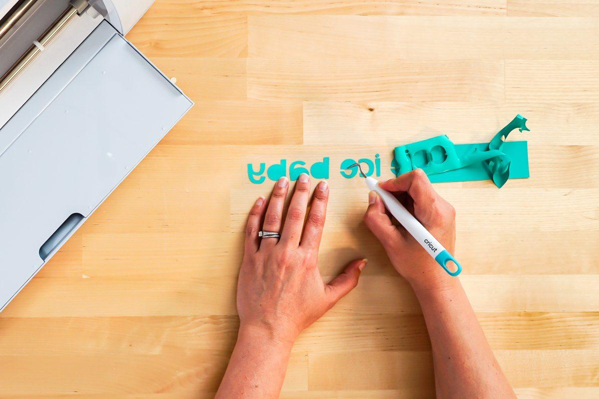 Hands weeding iron on vinyl