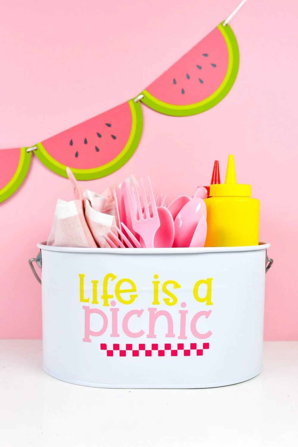 White picnic caddy with Life is a Picnic decal, filled with picnic supplies on a pink watermelon background.