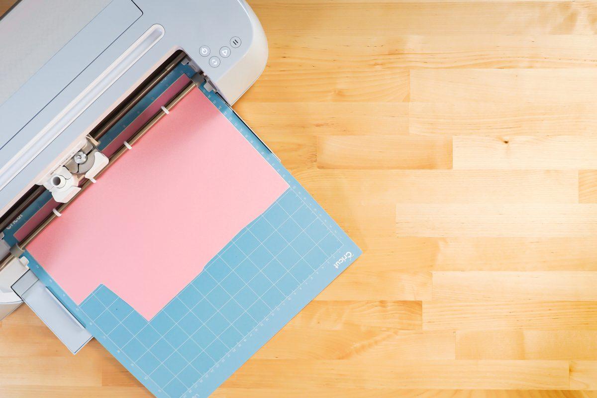 Cricut Maker 3 cutting pink vinyl on mat.