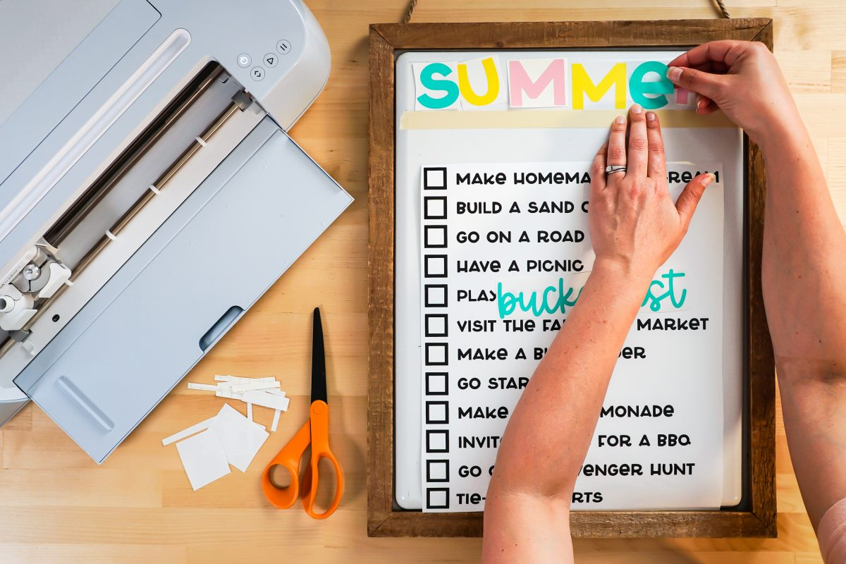 """Hands manually adding the word """"SUMMER"""" to the top."""
