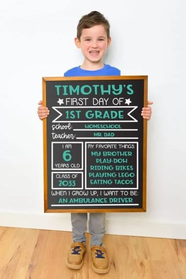 Young boy holding chalkboard sign against white background