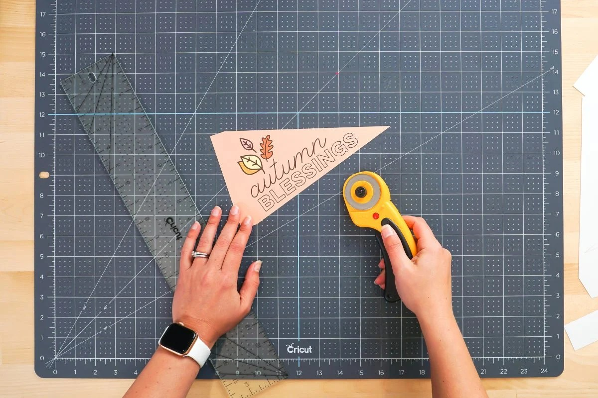 Hands showing cut pennant with rotary blade and ruler.
