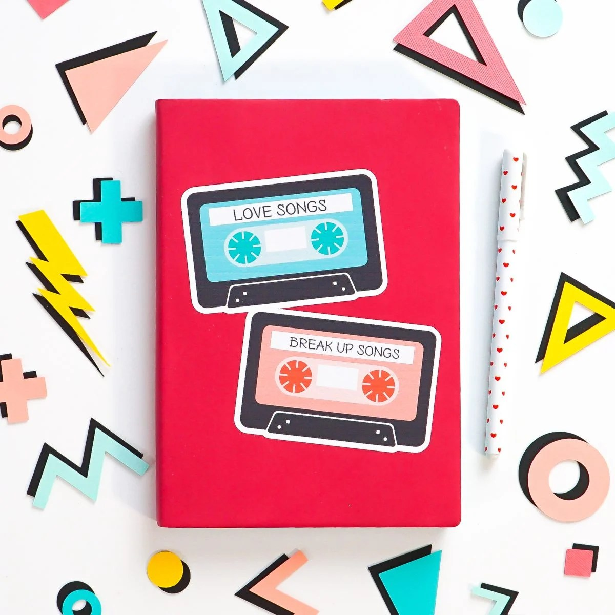 Pink notebook with big mix tape sticker, surrounded by 80's shapes