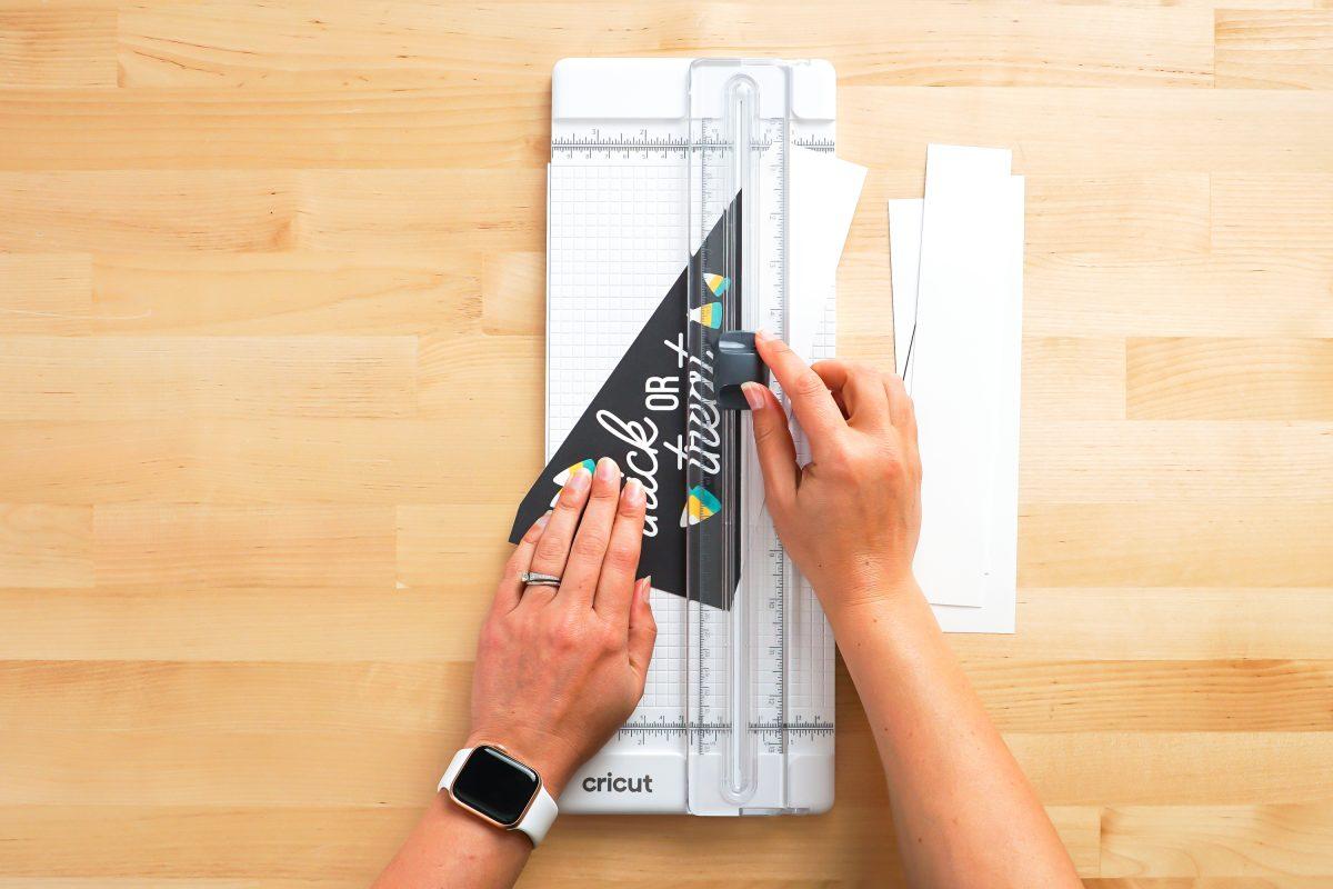 Hands cutting Halloween pennants using paper cutter