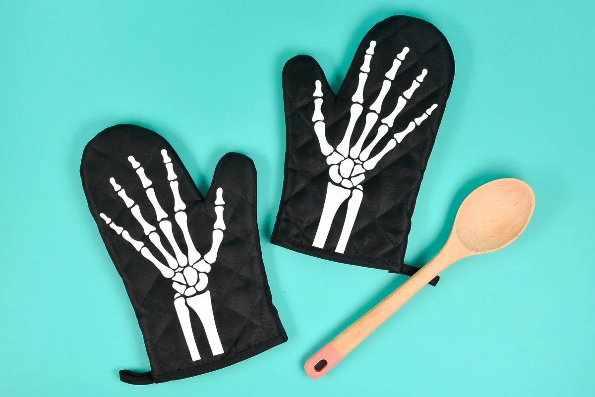 Skeleton oven mitts with spoon on teal background.