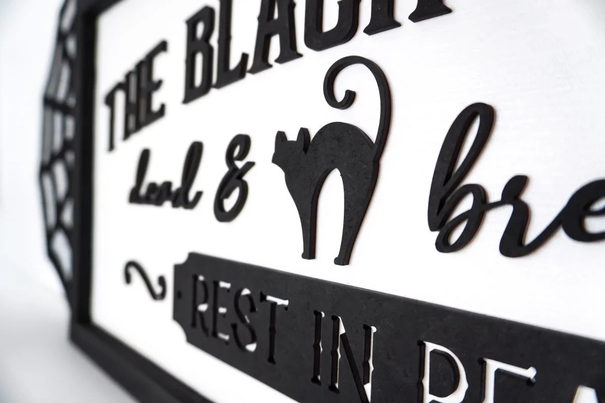 Angle shot of Vintage Halloween Sign: Black Cat Inn sign styled on shelf with Halloween decor
