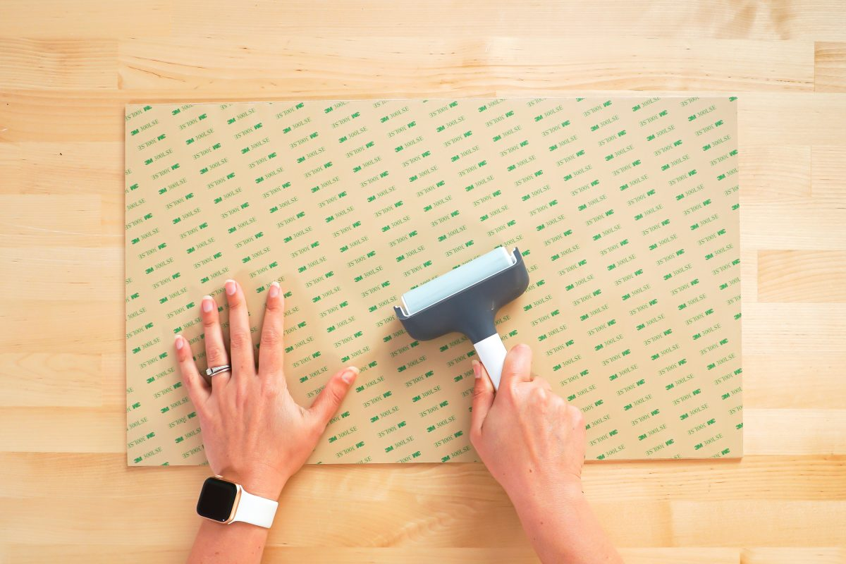 Hands using brayer to adhere 3M adhesive to back of draftboard.