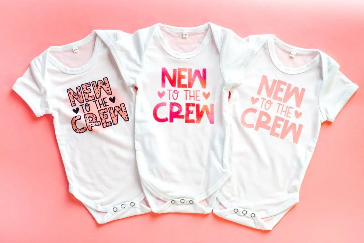 """Three onesies with """"new to the crew"""": sublimation, infusible ink, htv"""
