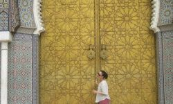 woman in front of large Moroccan doors