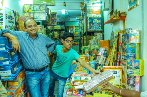 """A fire cracker seller gleefully poses with his son during Diwali season. """"This is the main season when we earn the most. Even foreigners buy our crackers these days says Rangarajan"""""""
