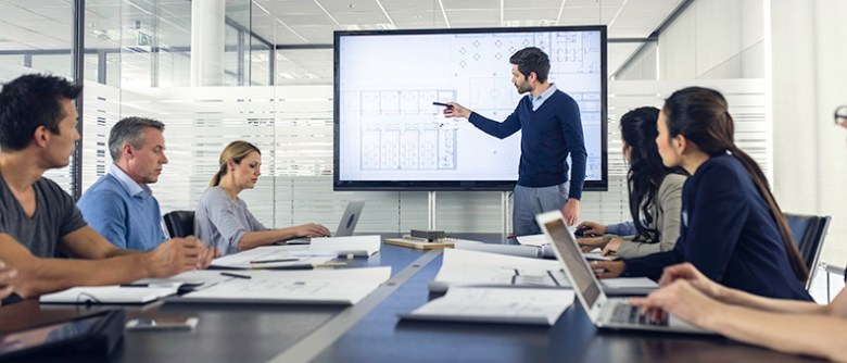 Engineer standing in front of a presentation screen and pointing to it while explaining details to the audience.