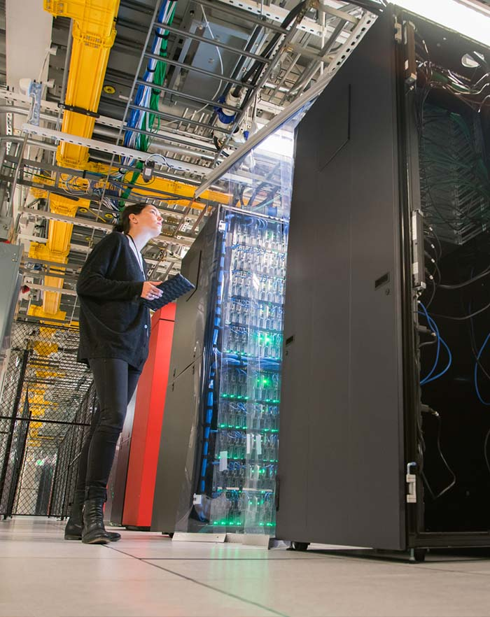 Image of woman technician looking after modern server room