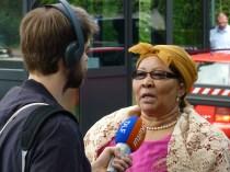 """Ida Hoffmann, Mitglied im namibischen Parlament und namibische Parlamentsabgeordnete und Vorsitzende des »Nama Technical Genocide Committee« : """"Ich bin sehr enttäuscht darüber, dass wir trotz Ankündigung unseres Besuchs vom Bundespräsidenten nicht einmal hineingebeten und schon am Eingangstor abgefertigt wurden. Geht man so mit den Nachfahren von Opfern eines Genozids um? Ich sorge mich sehr um die namibisch-deutschen Beziehungen: Die herablassende Haltung des deutschen Staates ist heute leider erneut deutlich geworden - wir werden sehen, wie die namibische Regierung darauf reagiert, dass ihre Bürgerinnen und Bürger hier derart behandelt werden. Unser Dank gilt den Organisatoren des Appells """"Völkermord ist Völkermord"""" in Deutschland, der ohne Zweifel einen Durchbruch darstellt."""" 6.7.2015 (Foto: A. Bohne)"""