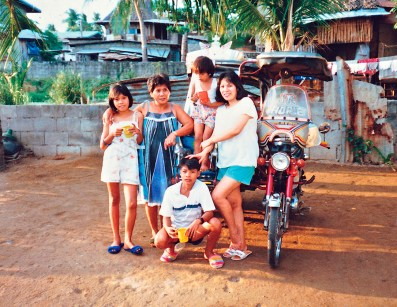 Socorro left her family and homeland to find better opportunities but the Philippines remained close to her heart. She visits as often as possible and sends support to her large extended family. Socorro's sister Segunda and children with their motor tricycle in Malolos, 1989. (Socorro Alfonso Collection)