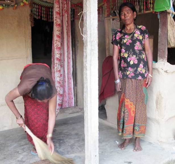 Sita Kumal sweeps the front porch of their house as Ramkumari Kumal, her mother-in-law, looks on  Photo: ICIMOD
